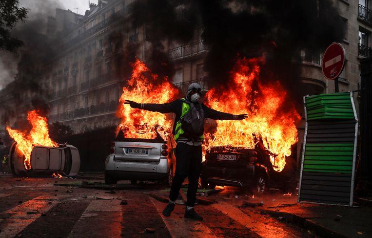 Brandende auto's bij protest door de gele hesjes in Parijs. In de welvaartslanden is pessimisme koning. België kende in de bevraging zelfs het grootste aandeel mensen (49 procent) die overtuigd zijn dat de leefomstandigheden slechter worden in de toekomst. Beeld EPA