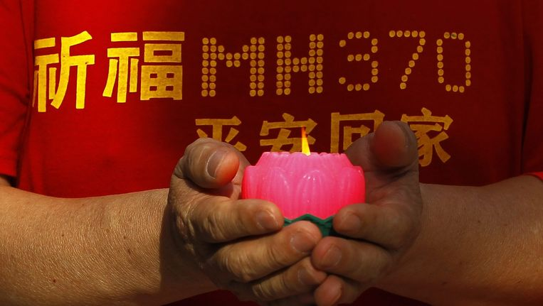 Een man brandt een kaarsje voor de slachtoffers van vlucht MH370 Beeld ANP