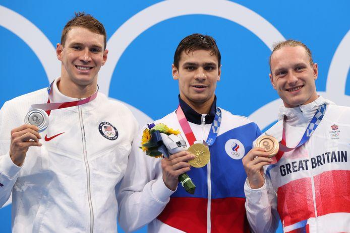 Evgeny Rylov toont zijn gouden medaille, links de zilveren Ryan Murphy, rechts de bronzen Luke Greenbank.