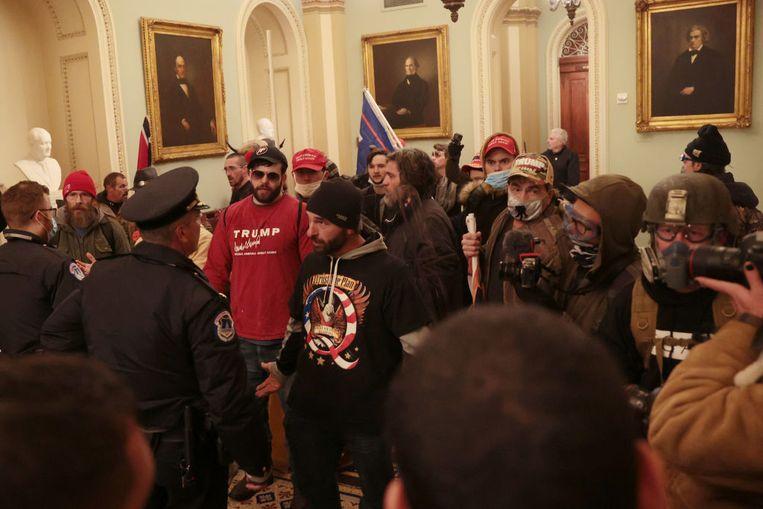 Demonstranten komen in het Capitool tegenover de politie te staan Beeld Getty Images