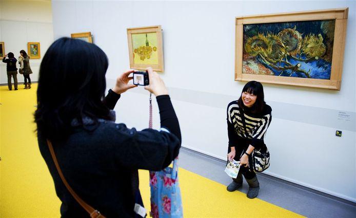 Een vrouw laat zich fotograferen bij het schilderij Vier uitgebloeide zonnebloemen van Vincent van Gogh in het museum Kröller-Müller.