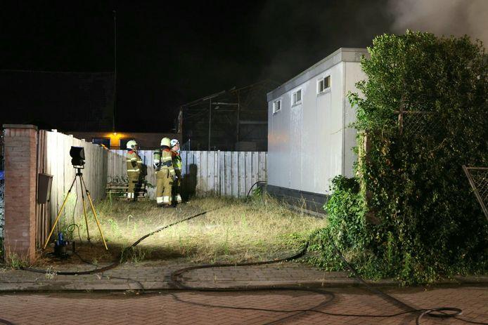 Brandweerlieden blussen de brand. Op de achtergrond is de hal, die vorig jaar op 5 december afbrandde, te zien.