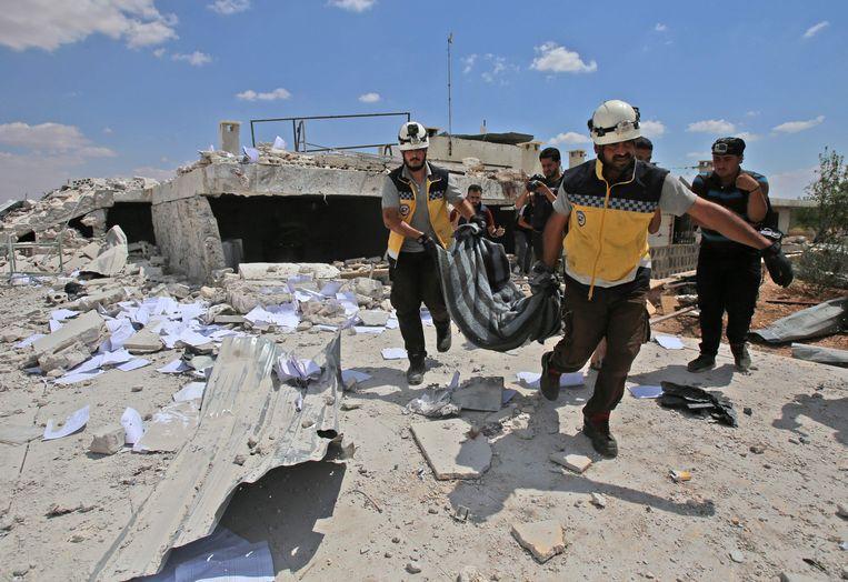 Leden van de Witte Helmen dragen het lichaam van een slachtoffer van een luchtaanval, woensdag, op een kliniek in de provincie Idlib.  Beeld AFP