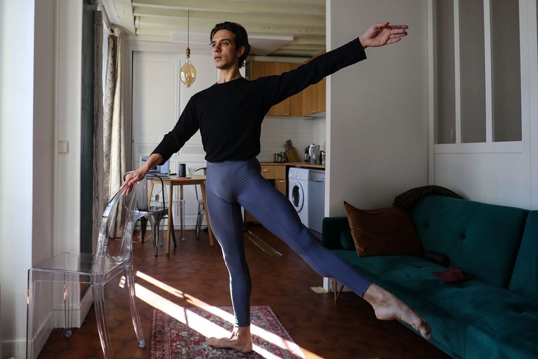 Ondanks de lockdown blijft de Italiaanse balletdanser Francesco Mura, verbonden aan de Opéra National de Paris, thuis in zijn appartement verder dansen.  Beeld AFP