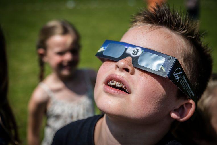 Zonsverduistering kijken met een eclipsbrilletje. Beeld Geert De Rycke