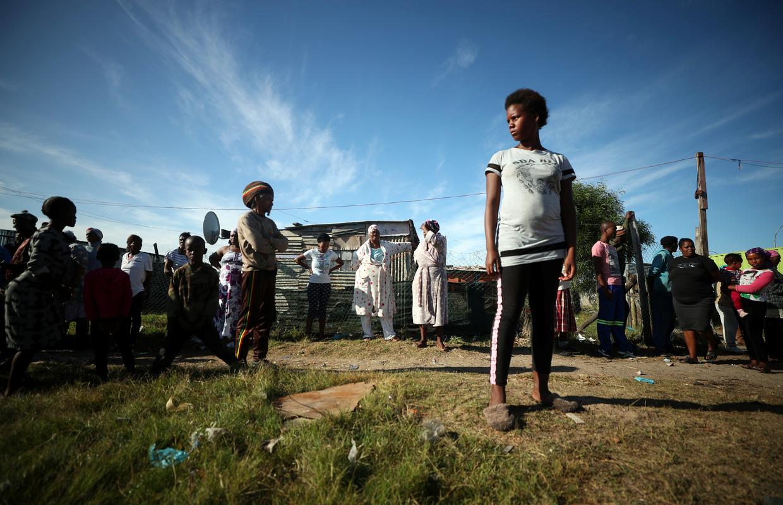 Rijen voor een voertuig van de overheid dat voedselpakketten uitdeelt in een Zuid-Afrikaans township.