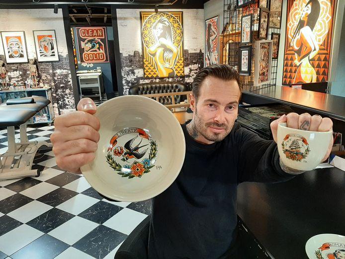 Tattoo-artist Robert Aalbers uit Waalwijk ontwierp de afbeeldingen op een servies dat binnenkort in de winkels ligt. Hier toont hij een proefversie. 'Uiteindelijk wordt het nog witter'.