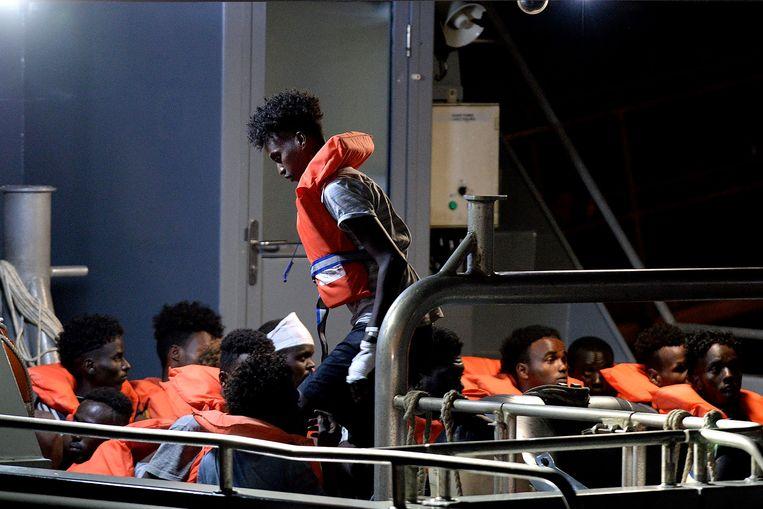 Migranten worden met een patrouillebootje aan land gebracht vanaf het reddingsschip Alan Kurdi.