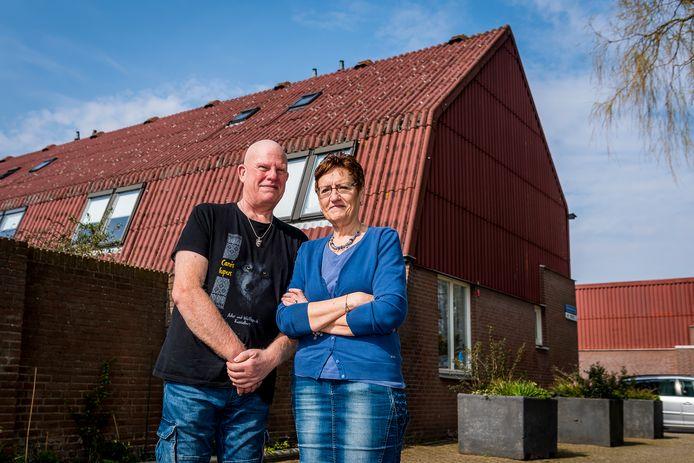 Miranda en Ron Schell, hier bij hun huis met asbestdak in de Rotterdamse wijk Beverwaard, vrezen op kosten te worden gejaagd als ze het dak moeten vervangen én andere woningaanpassingen moeten doen.