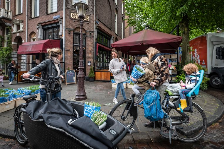 Lieve Nieuwint (met witte jas en blauwe spijkerbroek) en Vicky van der Spoel redden samen tulpen van de versnipperaar. Beeld Dingena Mol