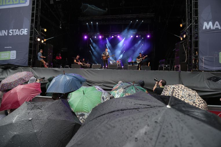 Yass op het podium van 'Genk on stage' vrijdagavond. Het publiek schuilt onder paraplu's.