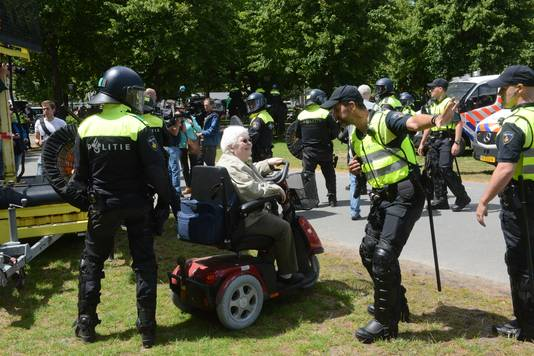 Politie communiceert met oudere vrouw op het Malieveld.