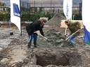 Denise (links) en Lonneke, leerlingen van praktijkschool De Brug in Zaltbommel, begraven een tijdcapsule op de plek waar nu hun nieuwe school gebouwd wordt.