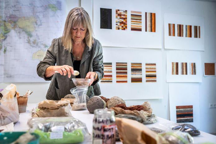 Kunstenares Elvira Wersche aan het werk met zand in haar atelier in Nuenen. Op de achtergrond hangen probeersels van het werk dat nu in de wandelgangen hangt van het tijdelijke onderkomen van de Tweede Kamer in Den Haag.