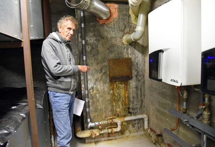 Paul van der Lingen wijst de plek aan in de kelder van de protestantse kerk in Sluiskil, schuin tegenover zijn woning, waar het water door de muur komt.
