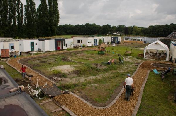 De ecodorpers wonen al vijf jaar in noodhuizen.