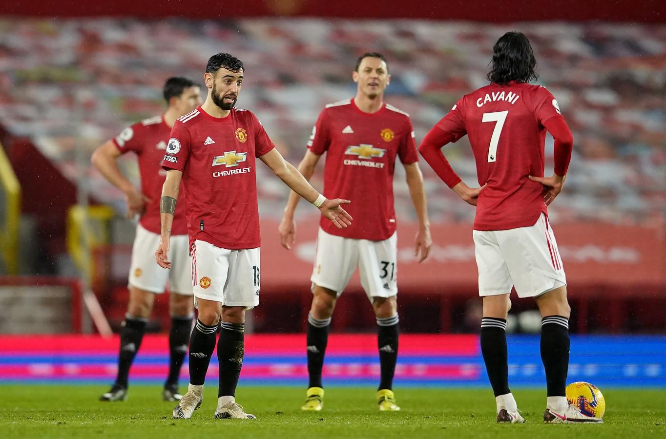 Bruno Fernandes (links) discussieert met ploeggenoten, onder wie Edinson Cavani.