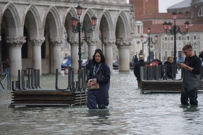 Toeristen waden door het water op het San Marcoplein in Venetië.