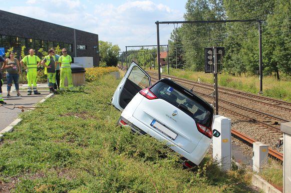 De Renault Scenic hangt erg schuin op het spoorwegtalud.