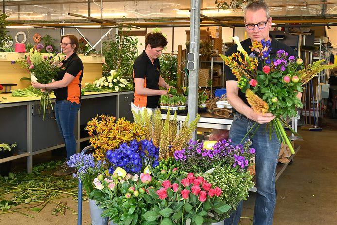 Druk bezig met het samenstellen van boeketten bij The Florist in Mill. Vlnr: Sanne Peters, Hera Gerrits en Herman Gerrits.