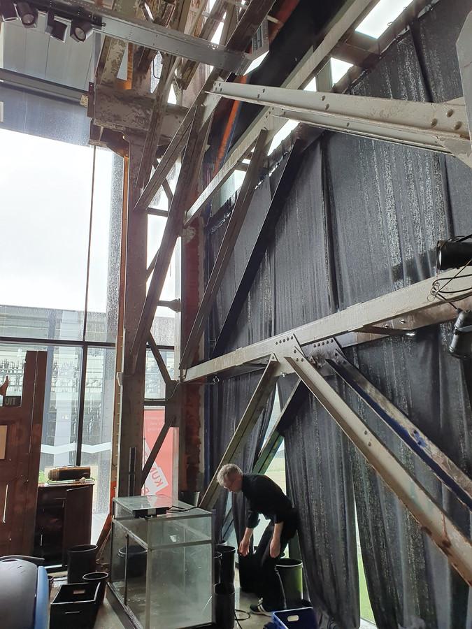In de hoek van Kunstloc Brabant loopt het regenwater langs de muren naar beneden. Medewerkers zijn bezig om het grootste deel van de lekkage op te vangen in emmers.