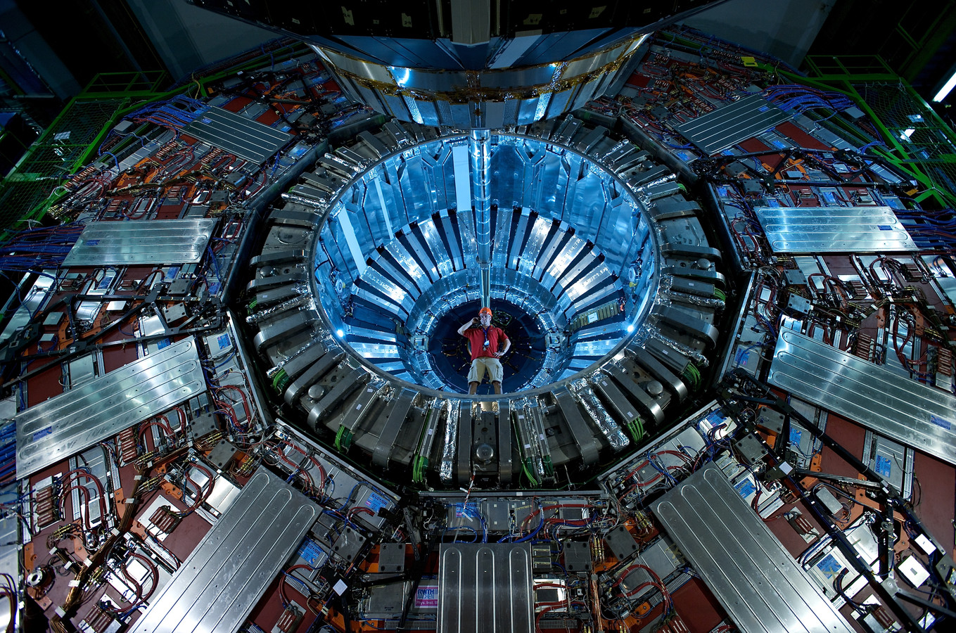 Een onderzoeker staat bij de Compact Muon Solenoid-detector, onderdeel van LHC.