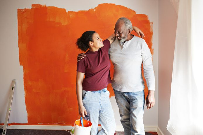 Smiling father and daughter standing with arms around against painted wall at home