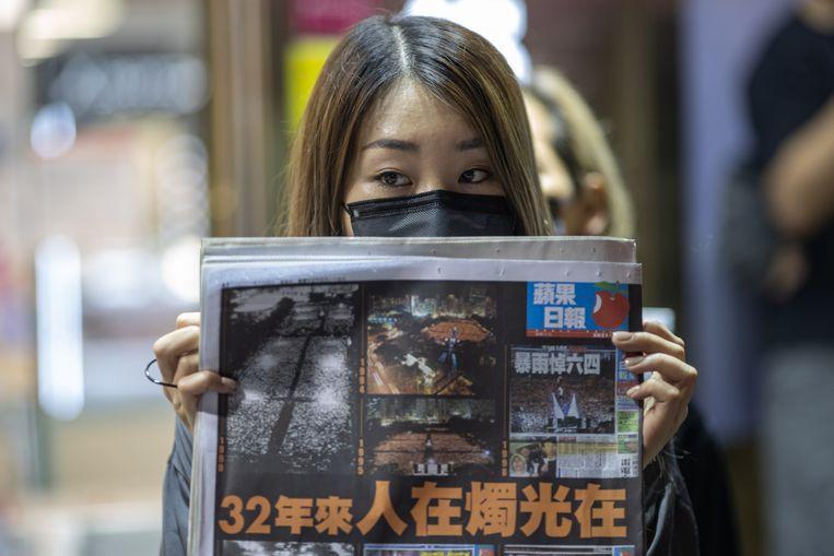 Een demonstrant in Hongkong houdt de voorpagina van de krant Daily Apple omhoog, begin deze maand. Beeld EPA