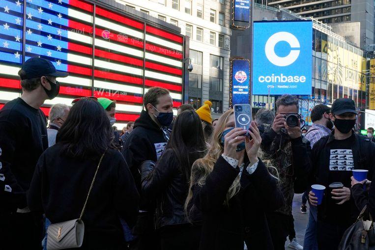 Medewerkers van Coinbase komen woensdag op Times Square in New York bijeen om de beursgang van hun bedrijf te vieren. Beeld AP