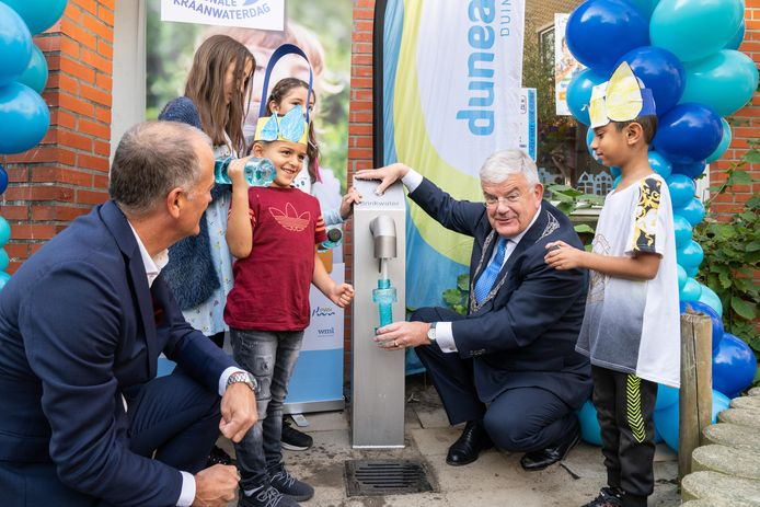 Directeur van Dunea Wim Drossaert met burgemeester Jan van Zanen tijdens opening van het eerste tappunt op een Haags schoolplein.