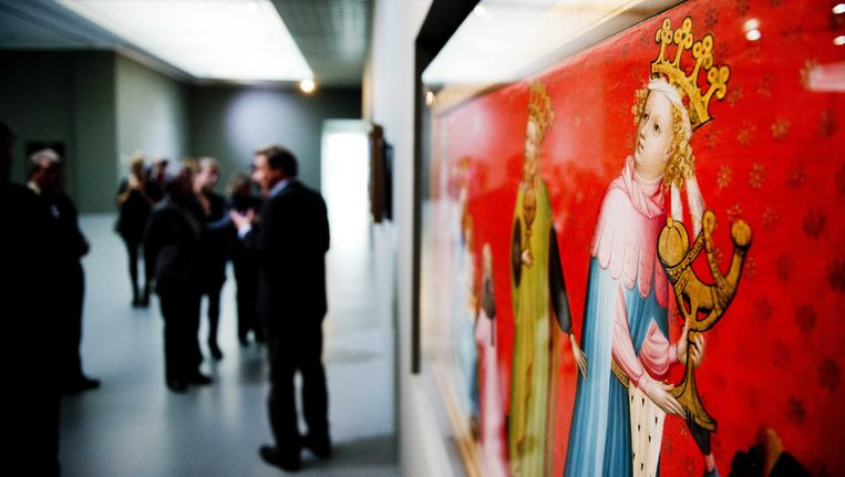 Bezoekers bij het werk De Aanbidding der Koningen van Jan van Eyck op de tentoonstelling De weg naar Van Eyck in het museum Boijmans van Beuningen Beeld ANP