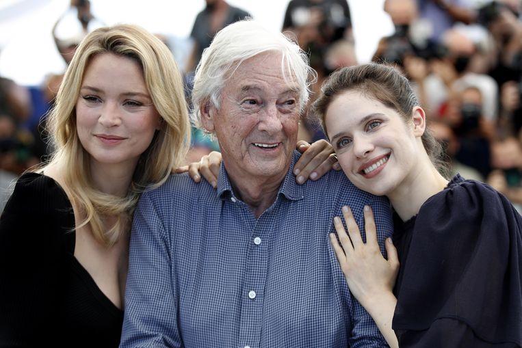 Paul Verhoeven, op het filmfestival in Cannes gefklankeerd door Benedetta-hoofdrolspeelsters Virginie Efira en Daphne Patakia. Beeld EPA