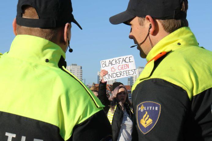 Onder toeziend oog van agenten demonstreren sympathisanten van actiegroep Kick Out Zwarte Piet (KOZP).