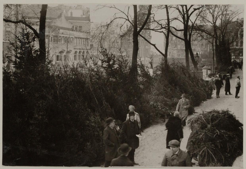 Verkoop van kerstbomen op de Bloemenmarkt, circa 1926. Aan de overkant van het water is de Munttoren te zien. Beeld Stadsarchief Amsterdam