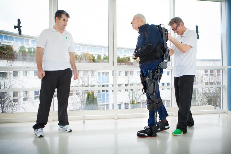 Een verlamde patiënt gebruikt een bionisch skelet waarmee hij kan lopen in een revalidatiecentrum gespecialiseerd in neurologisch herstel in Duitsland. Beeld UIG via Getty Images