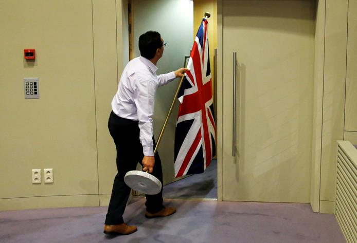 Een medewerker van het Europees Parlement in Brussel brengt een Engelse vlag naar een persconferentie.