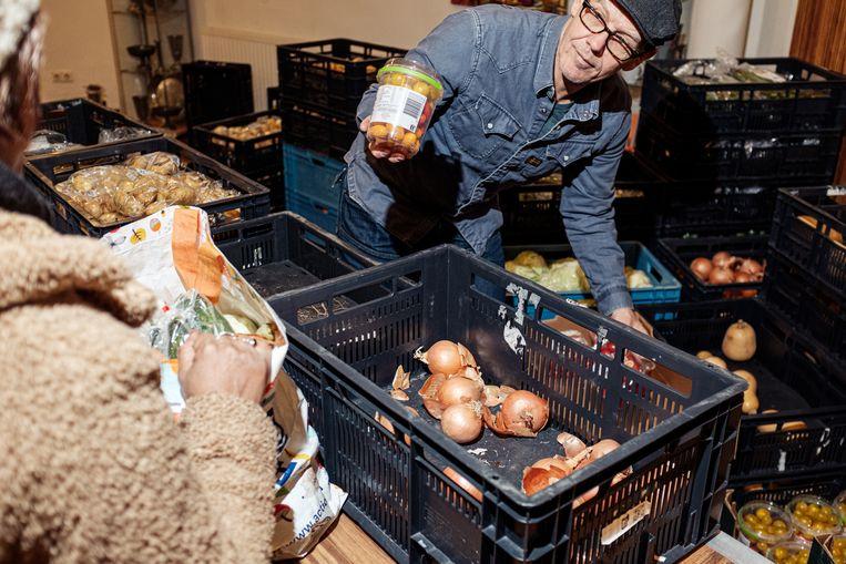 De nieuwe winkelopstelling in de Voedselmarkt aan de Lutmastraat (linksboven) en de oude manier van uitgeven van de Voedselbank in de Oranjekerk. Beeld Jakob Van Vliet