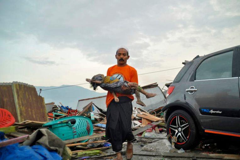 Een man draagt het lichaam van een kind dat om het leven is gekomen tijdens de tsunami.