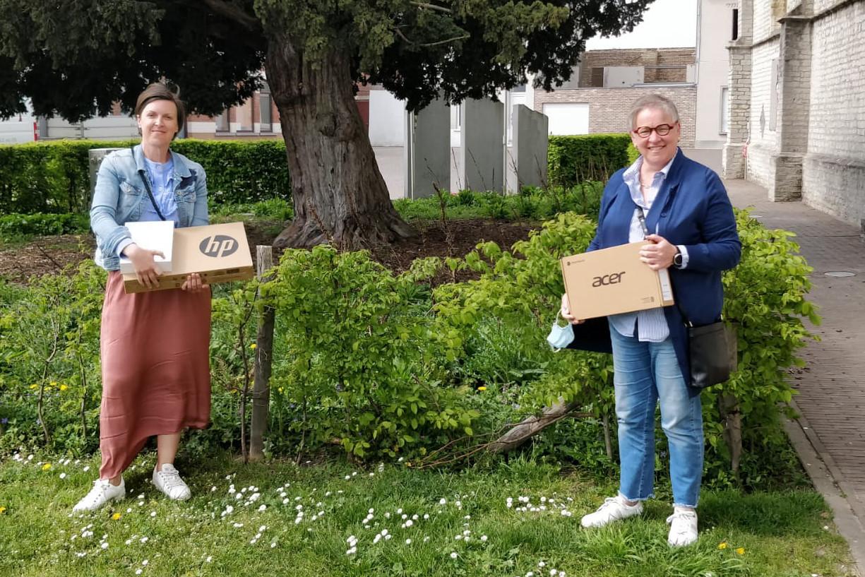 Creakindo-coördinator Hannelore Rosseel en onderwijsschepen Kathleen Hutsebaut brengen de computers naar de scholen.