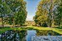 Vanuit de pas aangelegde zwemvijver geniet het koppel van een prachtig zicht op de Dendervallei.