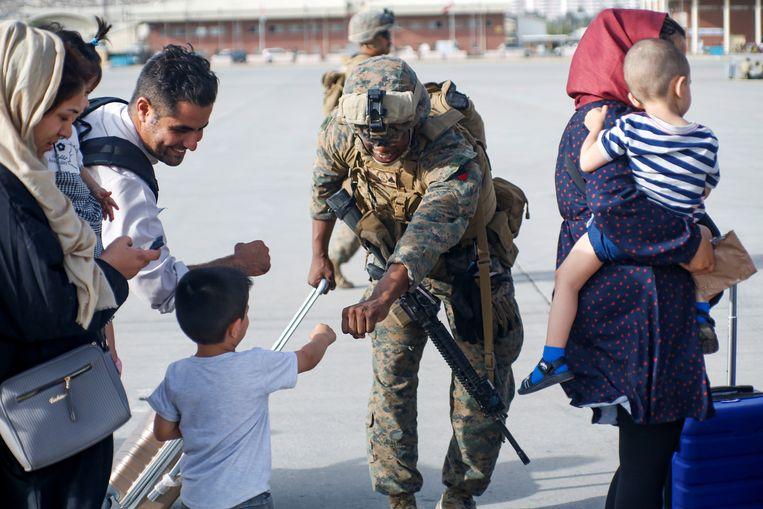 Een Amerikaanse soldaat en een Afghaans jongetje geven elkaar een vuistje op de luchthaven van Kaboel. Beeld via REUTERS