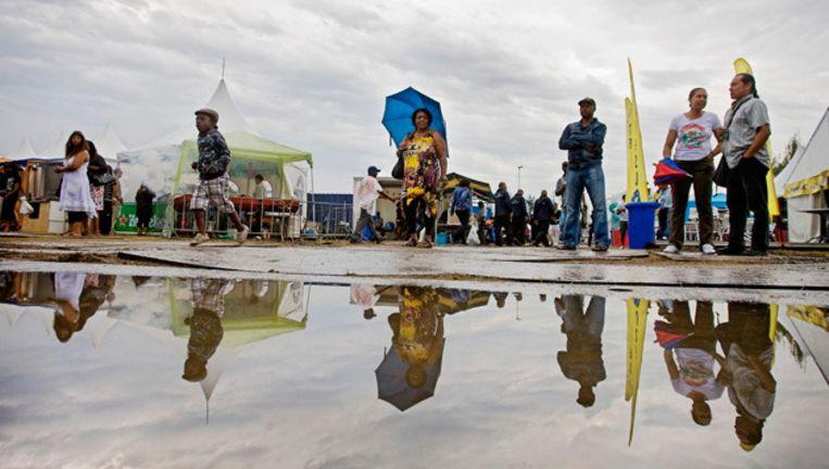 Bezoekers, vorig jaar, in de regen op de eerste dag van de 35ste editie van het Kwakoe Zomerfestival in het Bijlmerpark in Amsterdam-Zuid-Oost. Kwakoe begon in 1975 als een Surinaams voetbaltoernooi en groeide in de loop der jaren uit tot een van de grootste multiculturele festivals van Nederland. © anp Beeld