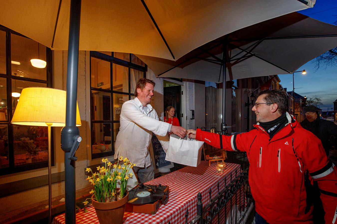 Tegen zonsondergang deelt chef Thomas van Santvoort voor de deur de thuismaaltijden uit aan de klanten die een diner hebben besteld.