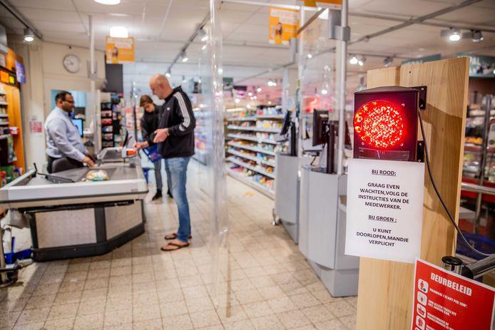 'Verkeerslicht' bij de ingang van een supermarkt om de stroom klanten te reguleren.