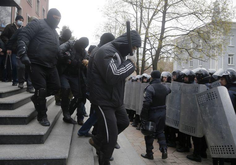 Pro-Russische activisten verlaten vanochtend het gebouw van de openbare aanklager in Donetsk. Beeld AP