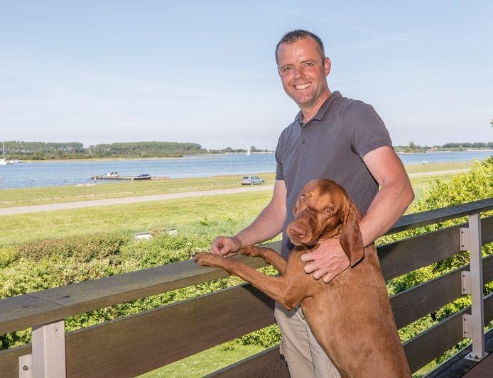 """Boer Maarten Janse, hier met Krijn - één van zijn drie honden. ,,Op mijn balkon met uitzicht op het Veerse Meer heb ik elke dag een vakantiegevoel."""""""