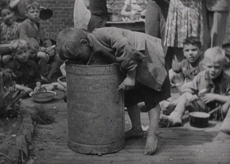 Een jongetje zoekt naar eten. Still uit de film Oorlog in Den Haag – Gefilmd Verleden 1940 – 1945 van het Haags Gemeentearchief. Beeld Haags Gemeentearchief
