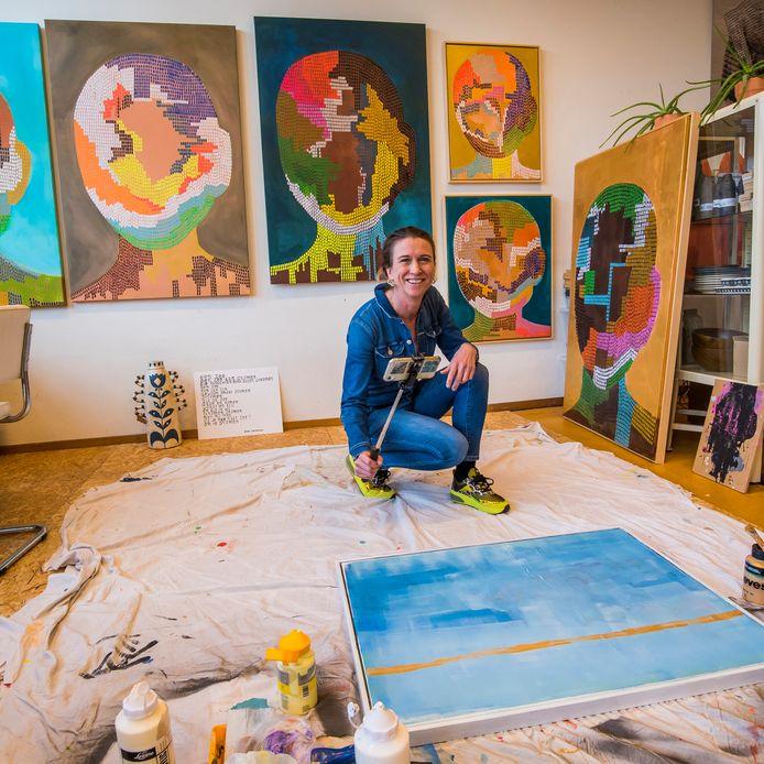 """Mikken met de selfiestick is een kunst op zich, weet Nathalie van Barneveld. De doeken achter haar hebben de titel What if ..? gekregen. De portrettenreeks is geïnspireerd op de Black Live Matters-beweging. ,,We zijn allemaal mens, gemaakt uit kleine blokjes DNA. All lives matter, dat is het idee erachter"""", licht Van Barneveld toe."""