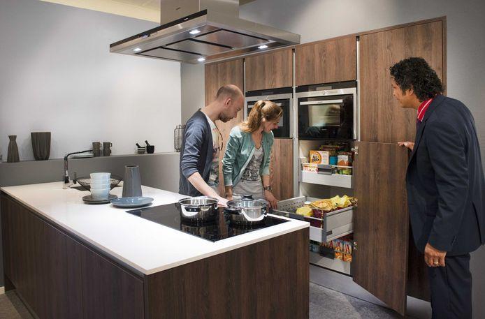 Een stel bekijkt onder toeziend oog van een verkoper een keuken in een keukenzaak.