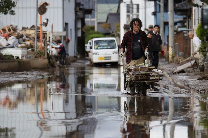 Een man ruimt rotzooi op rond zijn woning in Nagano, nadat tyfoon Hagebis is langsgekomen.